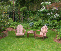 Close up of a small seating area in a large backyard garden
