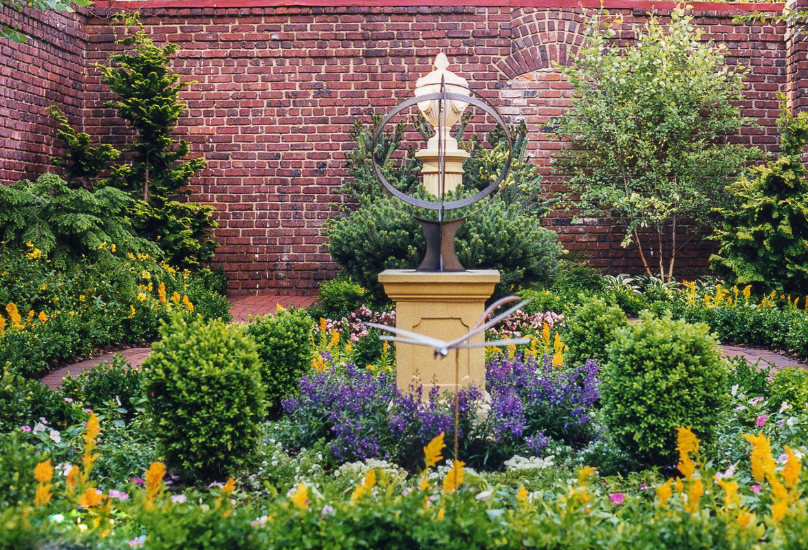 A mix of evergreens and annuals sets off a sundial. : Georgetown and Capitol Hill Gardens : CITYSCAPES® Landscaping Inc.