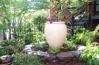 A circle of stone and a tall planter give vertical interest in this garden.