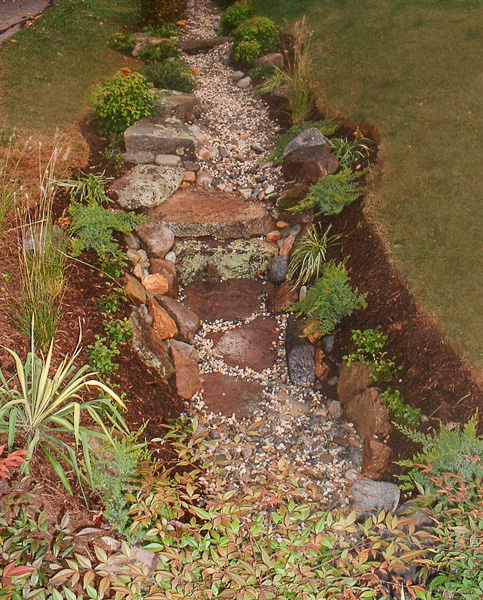 This dry stream bed along the front of the property is visually appealing and solves the mowing issue. : Suburban Gardens : CITYSCAPES® Landscaping Inc.