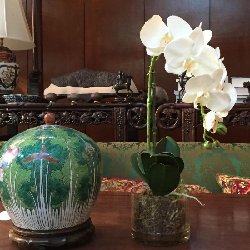 Faux orchid in glass container